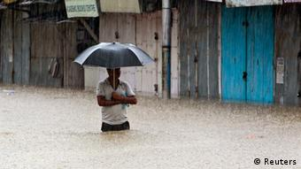 A man in Nepal wades through a flooded street with an umbrella (Photo: REUTERS/Jayanta Dey)