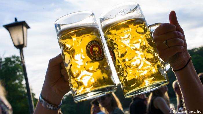 Zwei volle Bierkrüge, mit denen in einem Biergarten angestoßen wird