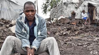 Theophilus Niwemyimana, a Congolese refugee seated on the ground.