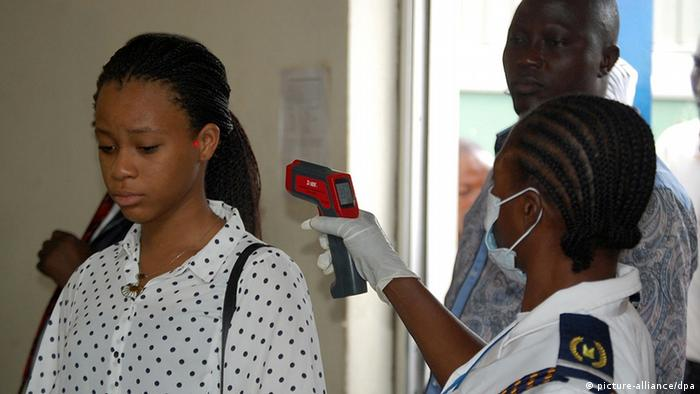 A female Nigerian health worker checks a passenger for fever symptoms at Abuja International airport
