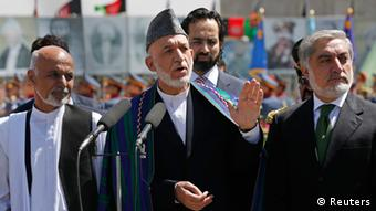 Afghan President Hamid Karzai (C) speaks during celebrations to commemorate Afghanistan's 95th anniversary of independence as he is flanked by presidential candidates Abdullah Abdullah (R) and Ashraf Ghani in Kabul August 19, 2014 (Photo: REUTERS/Omar Sobhani)