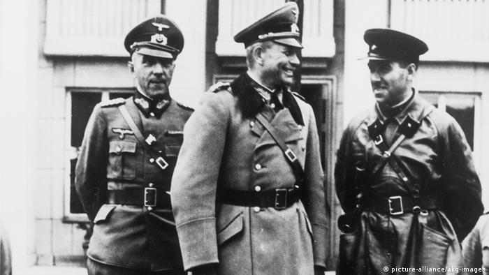 In a black-and-white photograph, Guderian and Krivoshein speak with another man