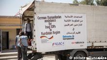 Helfer stehen am 16.08.2014 in Erbil im Irak beim Projekt der Diakonie in der A`shtar Schule, in der Flüchtlinge mit Lebensmitteln versorgt werden. Außenminister Steinmeier hielt sich zu einem eintägigen Besuch im Irak auf. Foto: Michael Kappeler/dpa