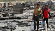 Syrian refugee children carry water bottles as they walk amid damage and the remains of tents for Syrian refugees that were burnt in the fighting between Lebanese army soldiers and Islamist militants in the Sunni Muslim border town of Arsal, in eastern Bekaa Valley August 9, 2014. Islamist militants holding 19 Lebanese soldiers seized during an incursion into Lebanon said on Friday they had demanded the release of Islamist prisoners in exchange for letting their captives go. Two commanders close to the group holding the soldiers, speaking by telephone, said the demands had been sent to the Lebanese government and army, which retook the border town of Arsal on Thursday after five days of fighting. REUTERS/Ahmad Shalha (LEBANON - Tags: POLITICS CONFLICT)