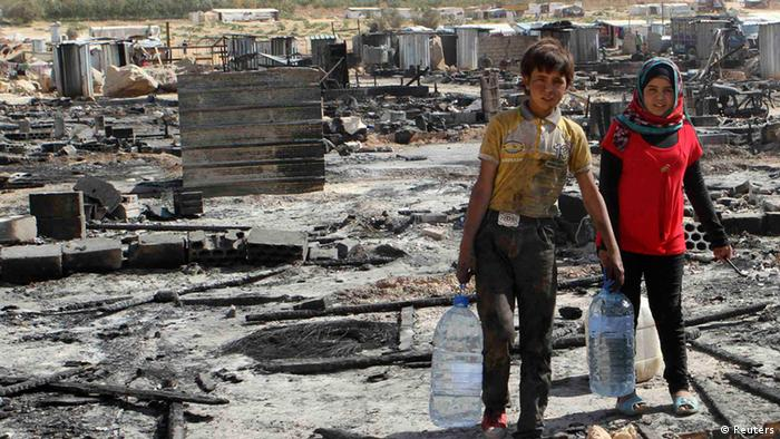 Syrian refugee children carry water bottles as they walk amid damage and the remains of tents for Syrian refugees that were burnt in the fighting between Lebanese army soldiers and Islamist militants in the Sunni Muslim border town of Arsal, in eastern Bekaa Valley August 9, 2014. REUTERS/Ahmad Shalha