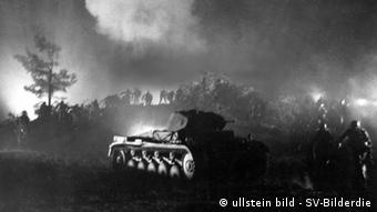 In a black-and-white picture, a tank rolls through bushes and trees.