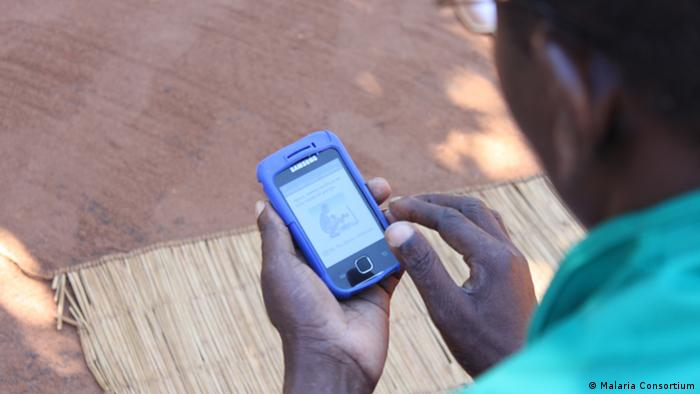 A health worker using his smartphone to track malaria