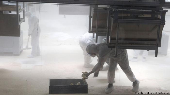 Спектакль кончается безмолвием: люди в респираторах сметают белую пыль