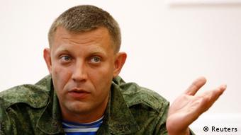 Alexander Zakharchenko, the prime minister of the Donetsk People's Republic, gestures off-camera while wearing army fatigues.