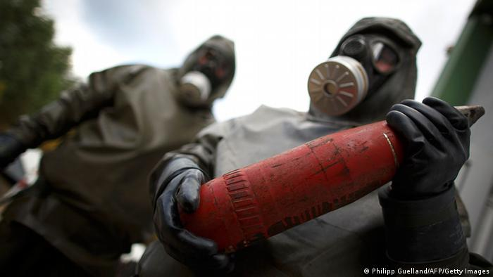 Workers in protective suits hold a dummy grenade in Munster, northern Germany.