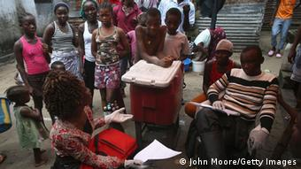 A lady seated and giving information to Liberians on how to prevent the spread of the Ebola virus.