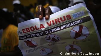 A hand holding a poster with information on how to prevent the spread of the Ebola virus.