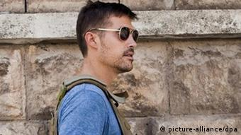 Wearing sunglasses anda bullet-proof vest, James Foley looks-off camera