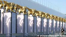 A passerby looks at Golden Lion statues, by Italian set designer Dante Ferretti, along the facade of the Cinema Palace in Venice, northern Italy, Monday, Aug. 30, 2004. The palace will host the 61st Venice International film festival, scheduled to run from Sept. 1 until Sept. 11. (AP Photo/Luigi Costantini)