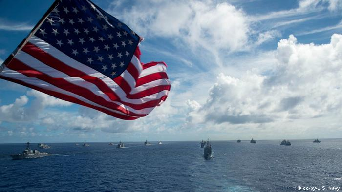 Aircraft carriers and US flag (cc-by-U.S. Navy)
