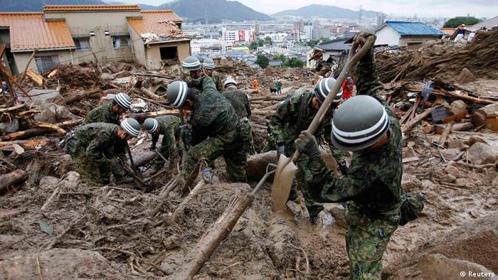 Japan Self-Defense Force (JSDF) soldiers search for survivors in the rain at a site where a landslide swept through a residential area at Asaminami ward in Hiroshima, western Japan. REUTERS/Toru Hanai