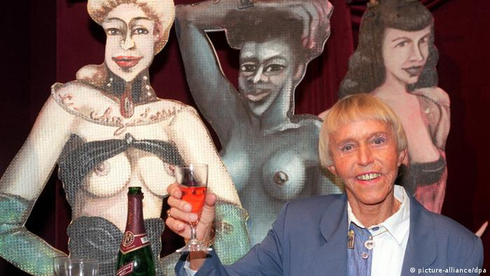 Beate Uhse poses with a glas in front of a painting of three women (picture-alliance/dpa)