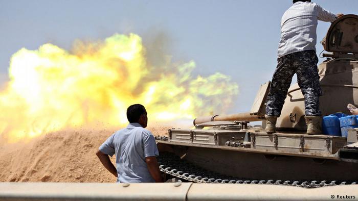 Men on tank as it fires