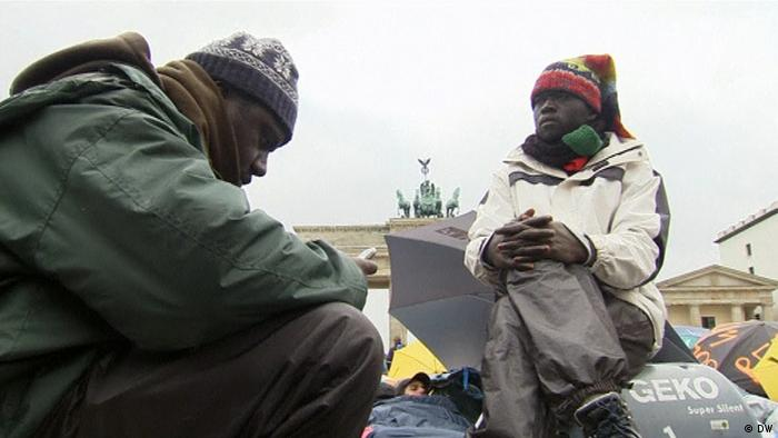 Two African refugees sit near the Berlin Brandenburg Gate
