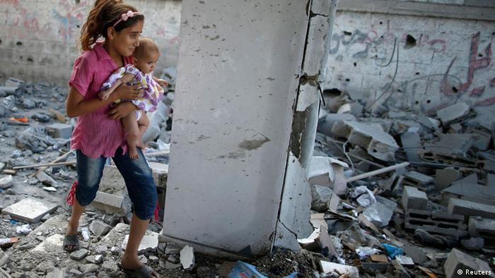 Ein palästinensisches Mädchen trägt seine Schwester durch den zerstörten Gaza-Streifen (Foto: Reuters)