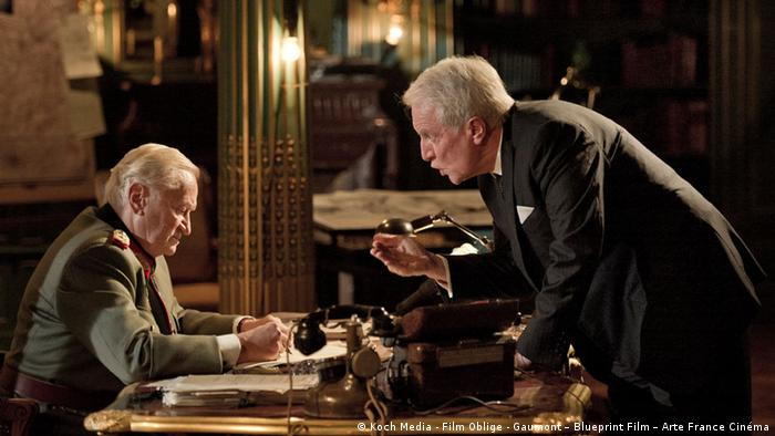 Ein älterer Mann beugt sich über einen Schreibtisch und redet energisch auf einen alten Mann in Nazi-Generalsuniform ein (Koch Media - Film Oblige - Gaumont – Blueprint Film – Arte France Cinéma)