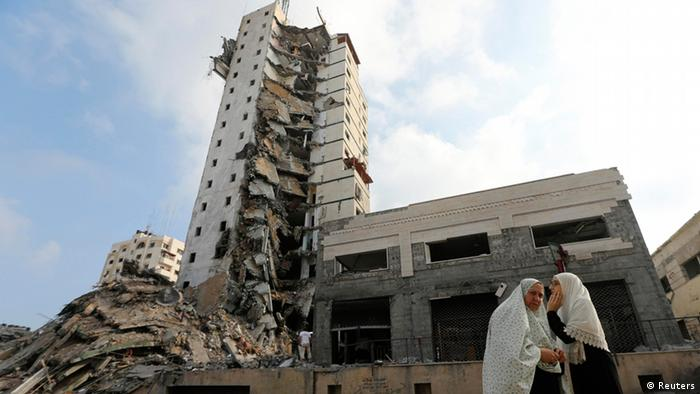 Palestinian women stand next to the remains of one of Gaza's tallest apartment towers, which witnesses said was hit by an Israeli air strike that destroyed much of it, in Gaza City August 26, 2014