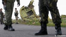 Armed pro-Russian separatists stand guard as monitors from the Organization for Security and Cooperation in Europe (OSCE) and members of a Malaysian air crash investigation team inspect the crash site of Malaysia Airlines Flight MH17, near the village of Hrabove (Grabovo), Donetsk region in this July 22, 2014 file photo. The United Nations' civil aviation body will launch two pilot projects designed to help airlines and states better share information about risks in conflict zones, the organization said on August 26, 2014 nearly six weeks after Malaysian airliner flight MH17 was shot down over Ukraine. REUTERS/Maxim Zmeyev/Files (UKRAINE - Tags: TRANSPORT DISASTER CIVIL UNREST)