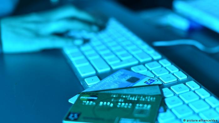 В полумраке кредитные карты лежат на компьютерной клавиатуре, на заднем плане человеческая рука