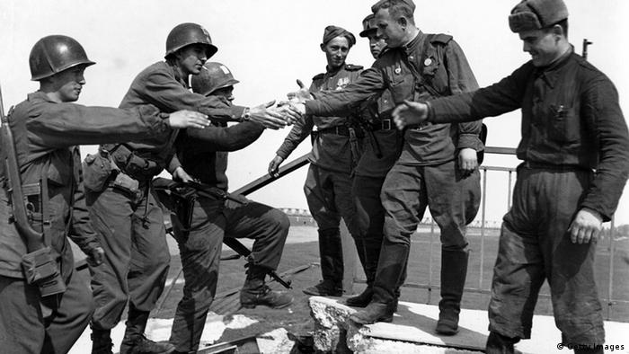 Soviet and US soldiers shake hands on a bridge on the Elbe River in 1945 (Getty Images)