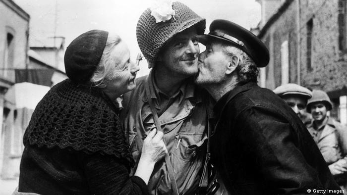 Dois idosos beijam soldado