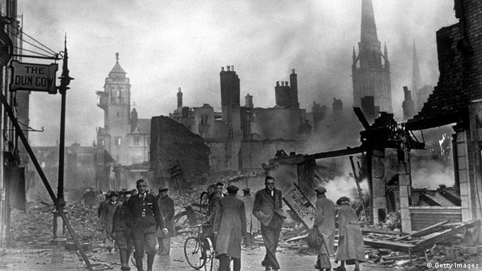 Pedestres numa rua com prédios completamente destruídos