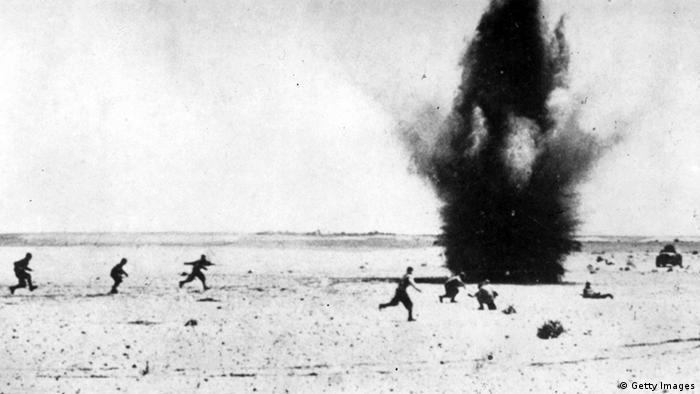 Pessoas correndo da explosão de uma bomba