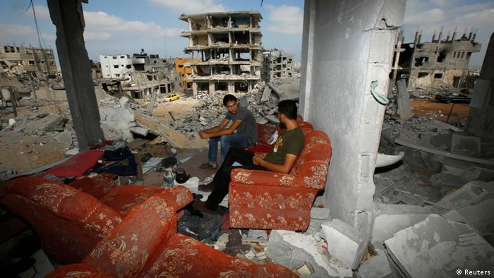 Palestinians sit on a couch as they return to the remains of their house, which witnesses said was destroyed in an Israeli offensive.