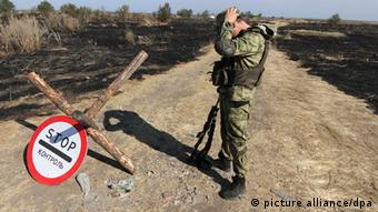 Ukrainian soldier stands where Ukrainian border guards had been on duty before they were allegedly fired on by Russian troops (photo: EPA/PHOTOMIG +++(c) dpa - Bildfunk)