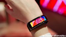 Eine Frau trägt am 11.03.2014 am Vodafone-Stand auf der Computermesse CeBIT in Hannover (Niedersachsen) eine Samsung-Smartwatch mit dem Namen «Samsung Gear Fit» an ihrer Hand. Die Uhr ist eine Neuheit von Samsung. Foto: Christoph Schmidt/dpa