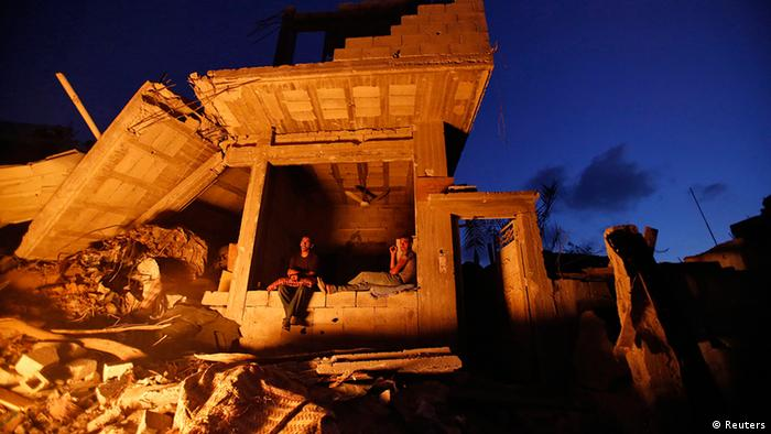 Palestinians sit outside their house. Witnesses said it was heavily shelled by Israel during the offensive, in the Shejaia neighbourhood, east of Gaza City in August 2014.