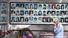 ITAR-TASS: BESLAN, RUSSIA. SEPTEMBER 1, 2014. A woman cries by the board with portraits of the victims of the siege at a memorial in School No.1 as she mourns the victims of the 2004 Beslan school siege. (Photo ITAR-TASS/ Stanislav Krasilnikov)