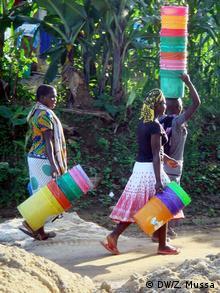 Girls carrying stacks of buckets walk down a sandy path. Photo: Zuberi Mussa