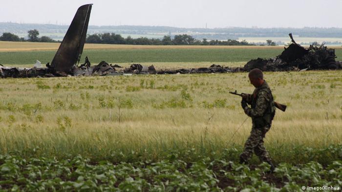 Soldado caminha, com avião destruído ao fundo, nos arredores do aeroporto de Lugansk