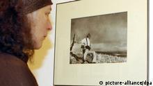 ARCHIV - Eine Besucherin betrachtet am 21.01.2005 in Berlin eine der wohl berühmtesten Aufnahmen des Fotografen Robert Capa, den Tod eines spanischen Milizionärs vom 05. September 1936 an der Front von Cordoba (Archivfoto). Tausende unveröffentlichte Negative des legendären Kriegsreporters Robert Capa (1913-1954) sind in Mexiko aufgetaucht. Die Bilder aus dem Spanischen Bürgerkrieg galten lange Jahre als verschollen, berichtete die «New York Times». Capa hatte sie in einen Koffer gepackt und vor dem Einmarsch der Deutschen 1940 in Paris zurückgelassen. Der gebürtige Ungar und spätere Gründer der Fotoagentur «Magnum» war bis zu seinem Tod in Vietnam selbst der Ansicht, die Negative seien zerstört worden. Foto: Stephanie Pilick dpa +++(c) dpa - Bildfunk+++