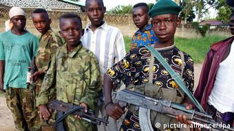 Teenage boy with machine gun standing among a group of younger children