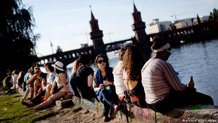 People sit along the banks of the Spree on a sunny day