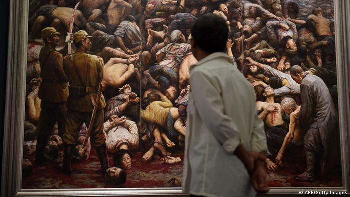 A visitor looks at a painting depicting the Nanjing massacre
