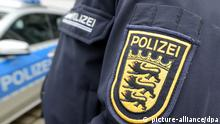 ILLUSTRATION - A the emblem of the police Baden-Wuerttemberg is seen on a policeman's jacket next to a police car in front of the police headquarters in Freiburg, Germany, 22 January 2014. Despite the legal dispute over 23 management posts police in the German state Baden-Wuerttemberg is not leaderless, according to Interior Minister Gall. Photo: Patrick Seeger/dpa