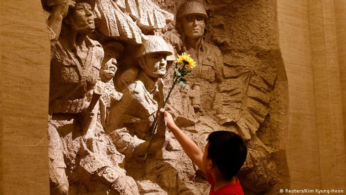 A boy places a flower on a sculpture depicting China's anti-Japanese war fighters during World War II