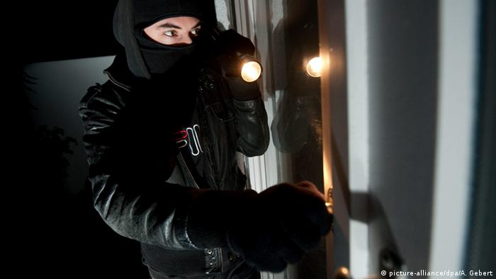 burglar in black with flashlight in the dark