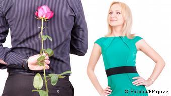 Symbolbild Liebespaar: ein Mann hält hinter seinem Rücken eine Rose fest, die Frau schaut ihn erwartungvoll lächelnd an