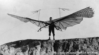 Der deutsche Luftfahrtpionier Otto Lilienthal steht mit seinem Fluggerät auf dem Rücken auf einem Berg