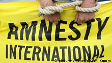 Aktivisten von Amnesty International protestieren am 28.07.2013 anlässlich der Wahlen in Mali auf dem Potsdamer Platz in Berlin. Amnesty will auf die alarmierende Menschenrechtslage und insbesondere die Häufung von Hinrichtungen in dem westafrikanischen Land aufmerksam machen. Foto: Wolfgang Kumm/dpa