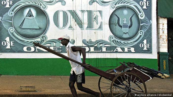 A man pulls a rikshaw alongside a wall painted with a huge dollar bill